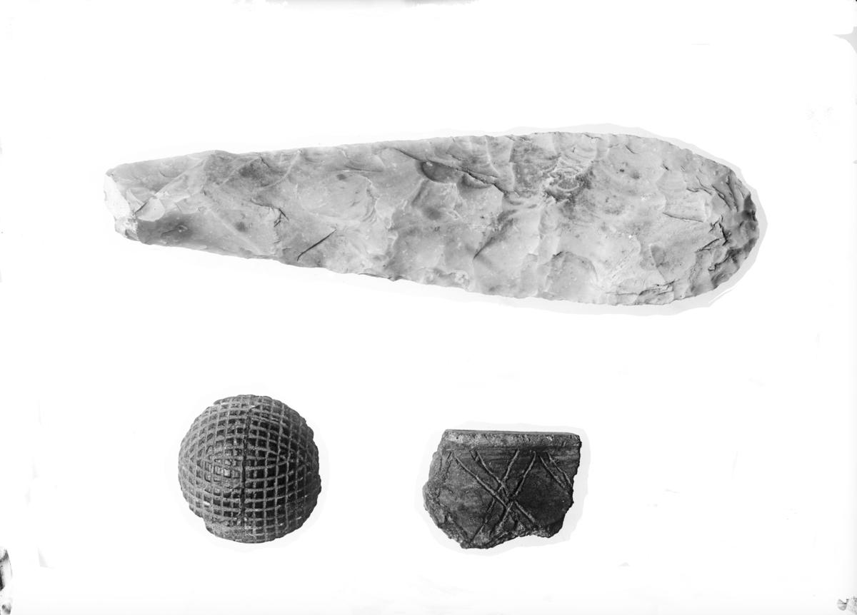 S6985) Overkantstykke av leirkar med et ornament bestående av del av en bord med dobbelte linjer som krysser hinannen. S7015) Kalottformet brikke eller knapp av svart jett, på den hvelvete overside et tett rutet ornamentmønster som fyller hele flaten. 3,7 cm i tverrmål, 1,4 cm tykk. S6972) Matkniv av flint, nærmest Vang Petersen.