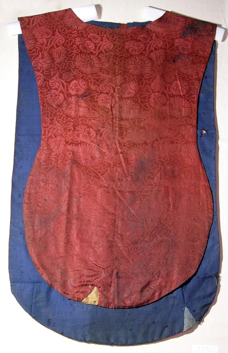 Sidendamast i 5-skaftad satin, röd. Varp: rött silke, ca 40 tr/cm Inslag: rött silke, ca 26 tr/cm Blad- och blommönster omgivet av mjuk slinga. Yllefoder i liksidig kypert (2/2), blått. Fodret lagat på några ställen med blått linnetyg, tuskaft. Mässhaken har axelsöm och är sydd av flera stycken. På baksidan 695 x 420 mm högt applicerat kors av 2 spetsar i metalltråd (spunnet lan, silver; lan, silver), tillsammmans 30 mm breda.