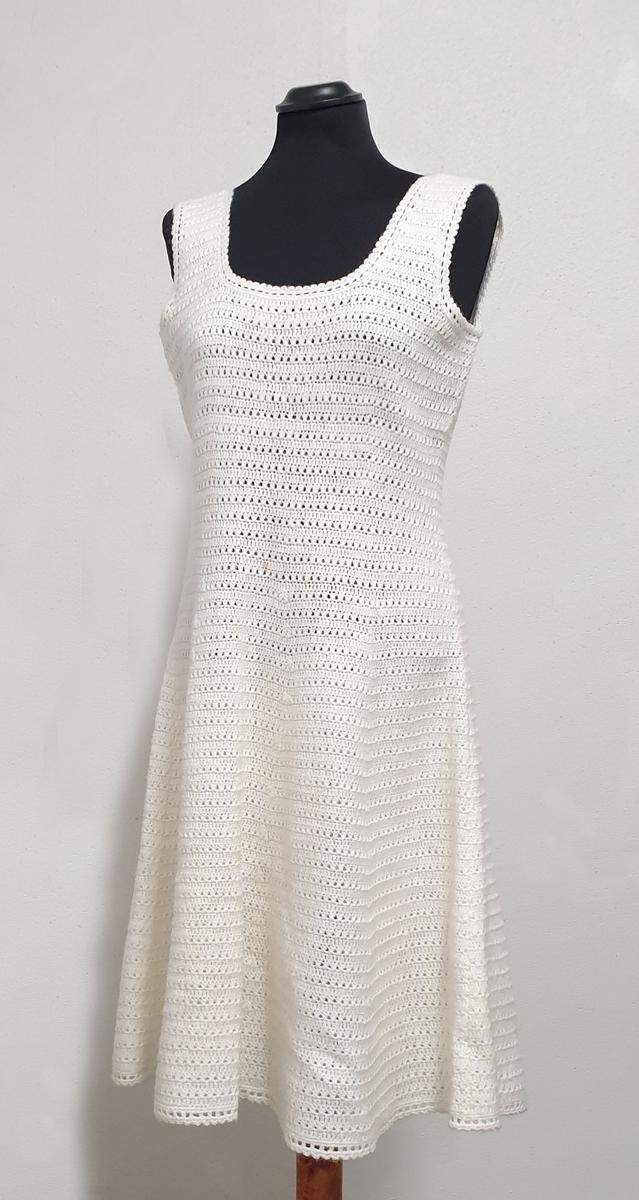 Hvit heklet drakt bestående av ermeløs kjole og jakke. Jakken har knapper i front, pyntelommer på hvert forstykke, skjortekrage og skulderputer. Flekk i front på både jakke og kjole.