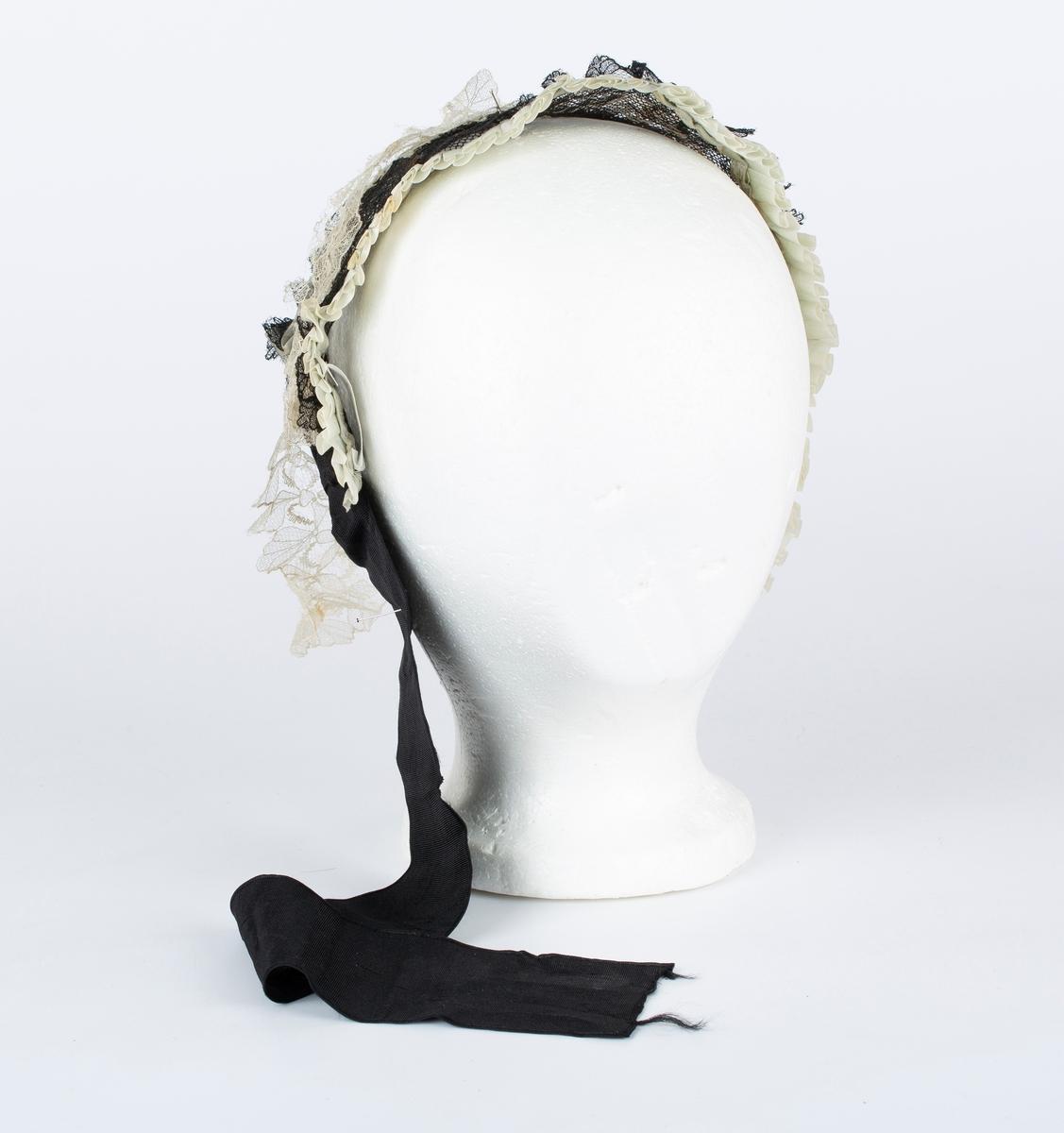 Sort og hvit blonde, tyll. Foldelagt silkebånd langs framkant.  Knytebånd i sort ripssilke, knyttebånd på venstre side mangler.  Blonder løsner, skjør.