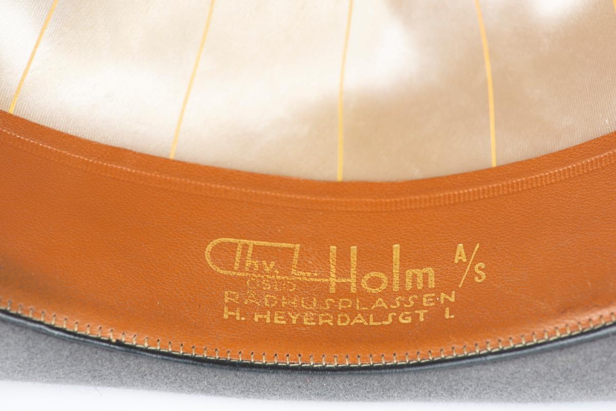 Herrehatt m/ bem vippet litt opp rundt hele. Pullen er oval og er innsunket oppå og foran på begge sider. Bånd rundt hatten i ovegangen brem-pull. Innvendig svettebånd merket JCB (Jens Christian Berg) Str. 59/ 7 !/2.