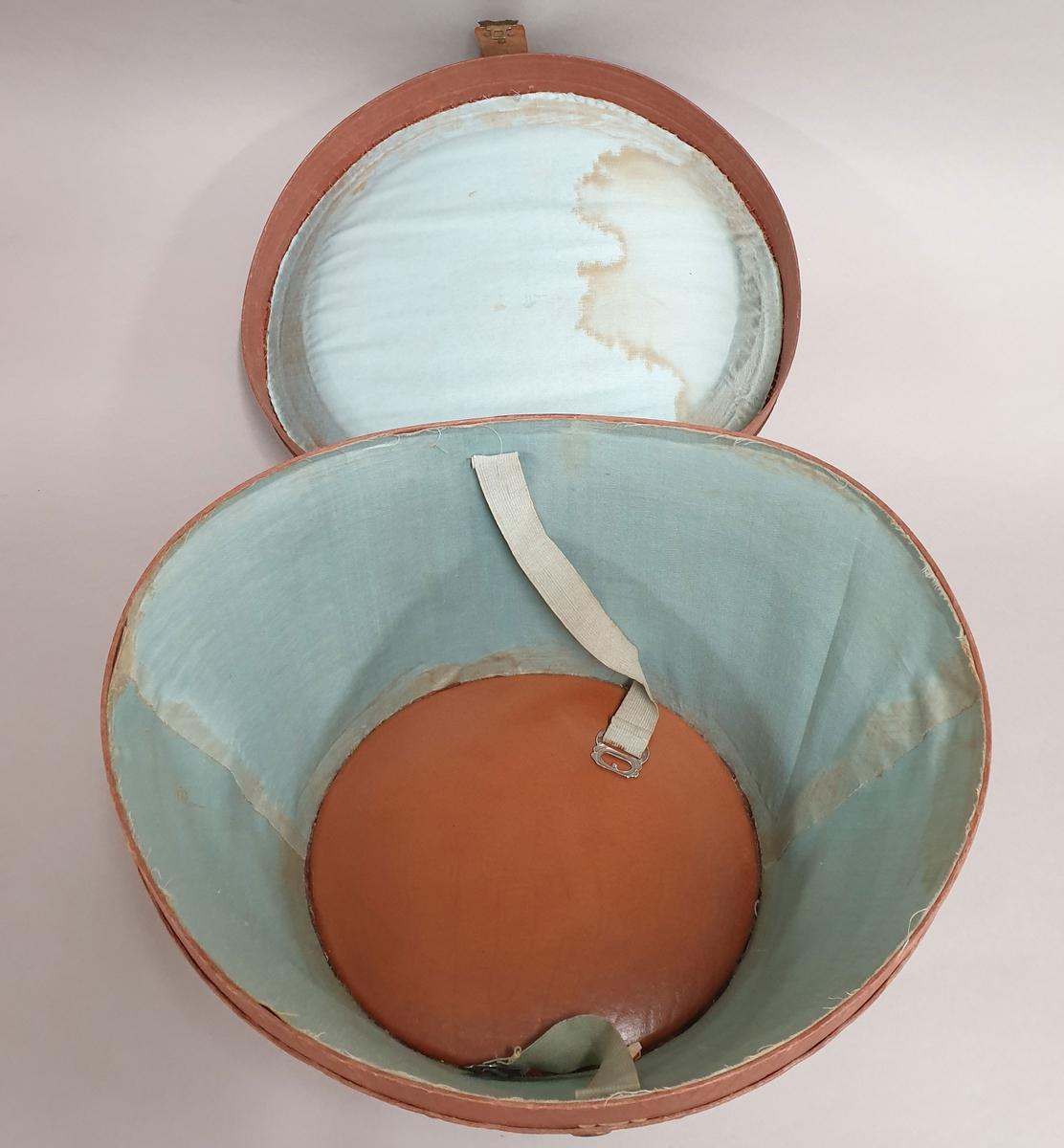 Hatteeske for flosshatt, av skinn. Lokket har håndtak og reim tvers over, med lås på siden av esken. Det er flere reiselapper av papir limt på esken.