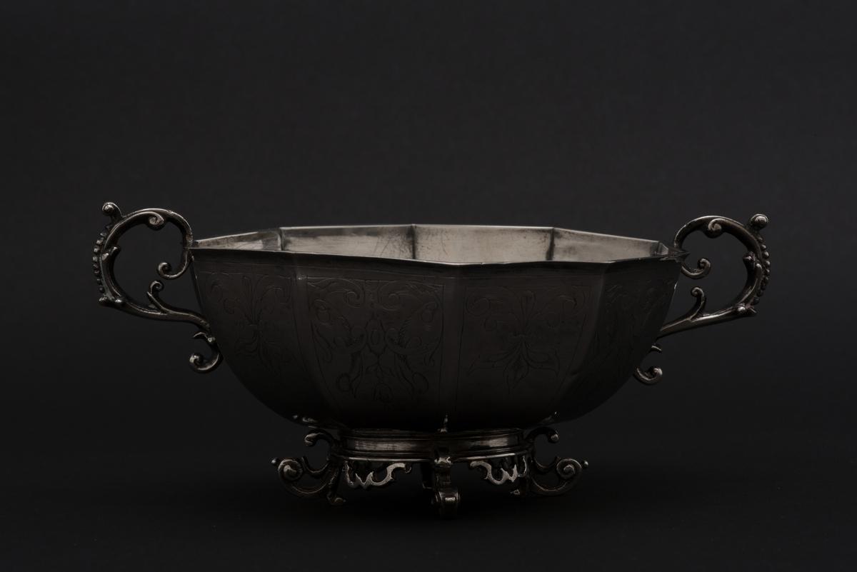 """Brännvinsskål av silver.  Dekagonformad skål (10-sidig cuppa) med fyra svängda fötter och två uppsvängda hänklar. Skålens tio fält har graverad dekor med blomstermotiv. Stämpeln på undersidan """"NN"""" har tolkats som Nils Nilsson, mästare i Linköping fram till 1673."""