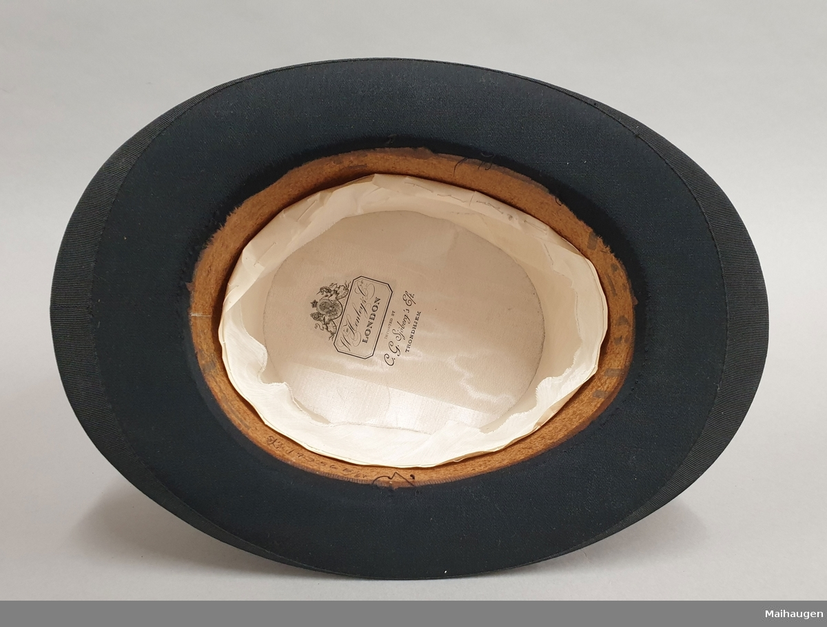 Flosshatt med overlate av svart pels, og med et bredt bånd av ullfilt med åtte små knapper på siden. Hvitt silkefôr med leverandørens emblem.  Hatteesken er av skinn med reimer på siden med spenner på lokket, og en reim som går tvers over lokket med lås på siden av esken. Håndtak på lokket. Esken er fôret med rød velour. Det er reiselapper av papir limt på lokket.