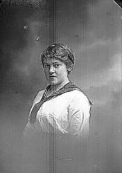 Bröstbild av en kvinna i ljus blus och sjömanskrage.