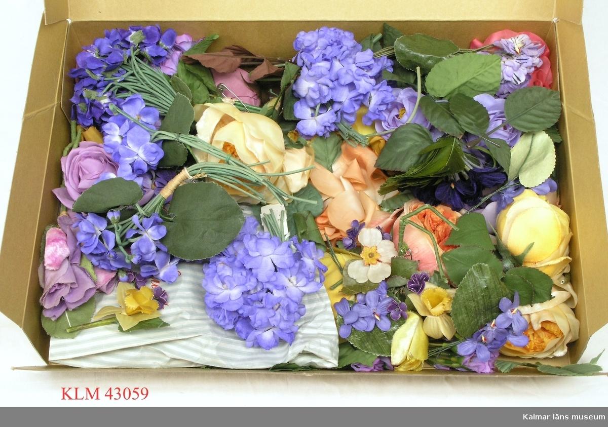 KLM 43059. Prydnadsföremål, tygblomma, en samling. Olika färger och sorter, både enstaka och buketter, av plast och textil. Bl.a. rosor, violer och liljekonvaljer. Troligen använda som bordsdekoration, både i hemmet och konditoriet. Eventuellt även som dräktdekor.