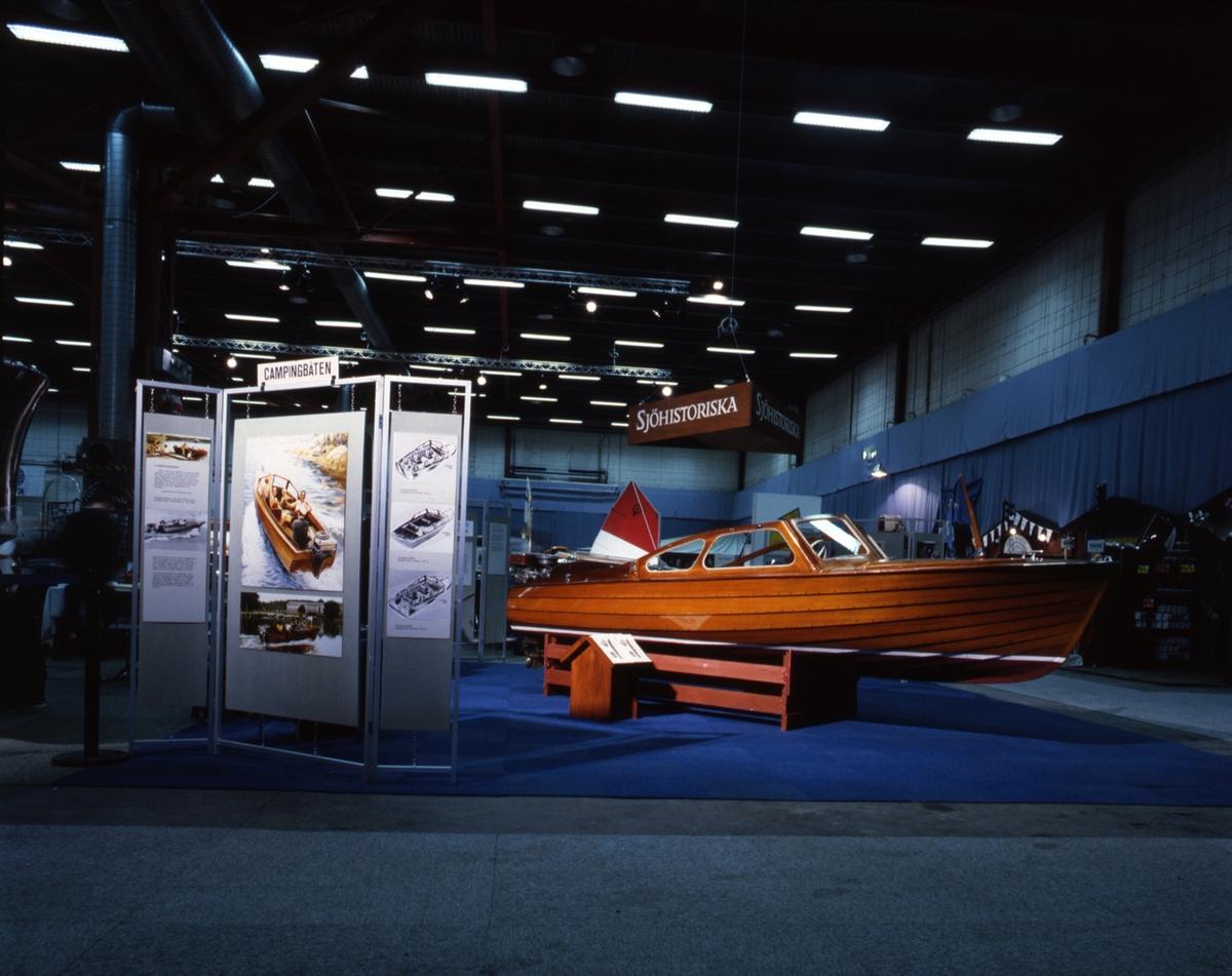 Campingbåt, klinkbyggd mahognymotorbåt med fördäck av oregonpine. Längd 5,12 meter. Bredd 1,72 meter. Rattstyrd. Fyra fasta stolar. Vindruta. Kapell. Saknar utombordsmotor. Stävskenan trasig. Tillverkad av Electrolux i Uppsala 1958.