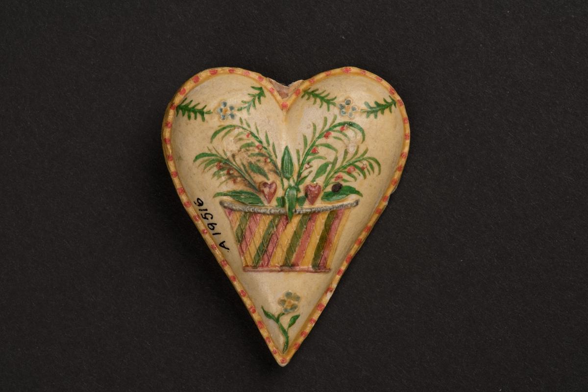Kotiljongsmärke, troligen av papier-maché, i form av ett stoppat hjärta. Hjärtat är dekorerat på bägge sidorna och har en kant målad i gult och rött. På den ena sidan avbildas en randig blomsterkorg som innehåller gröna blad och röda hjärtan under en girlang. På andra sidan är en palm under girlang. På denna sida finns även en inskrift i blyerts: Söderköping 1850.
