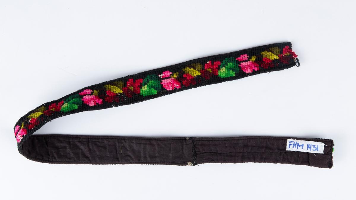Bånd. Korsstings ullbroderi på stramei. Bakside i sort stoff.  Motiv: Blomster og blader. Ukjent bruk.