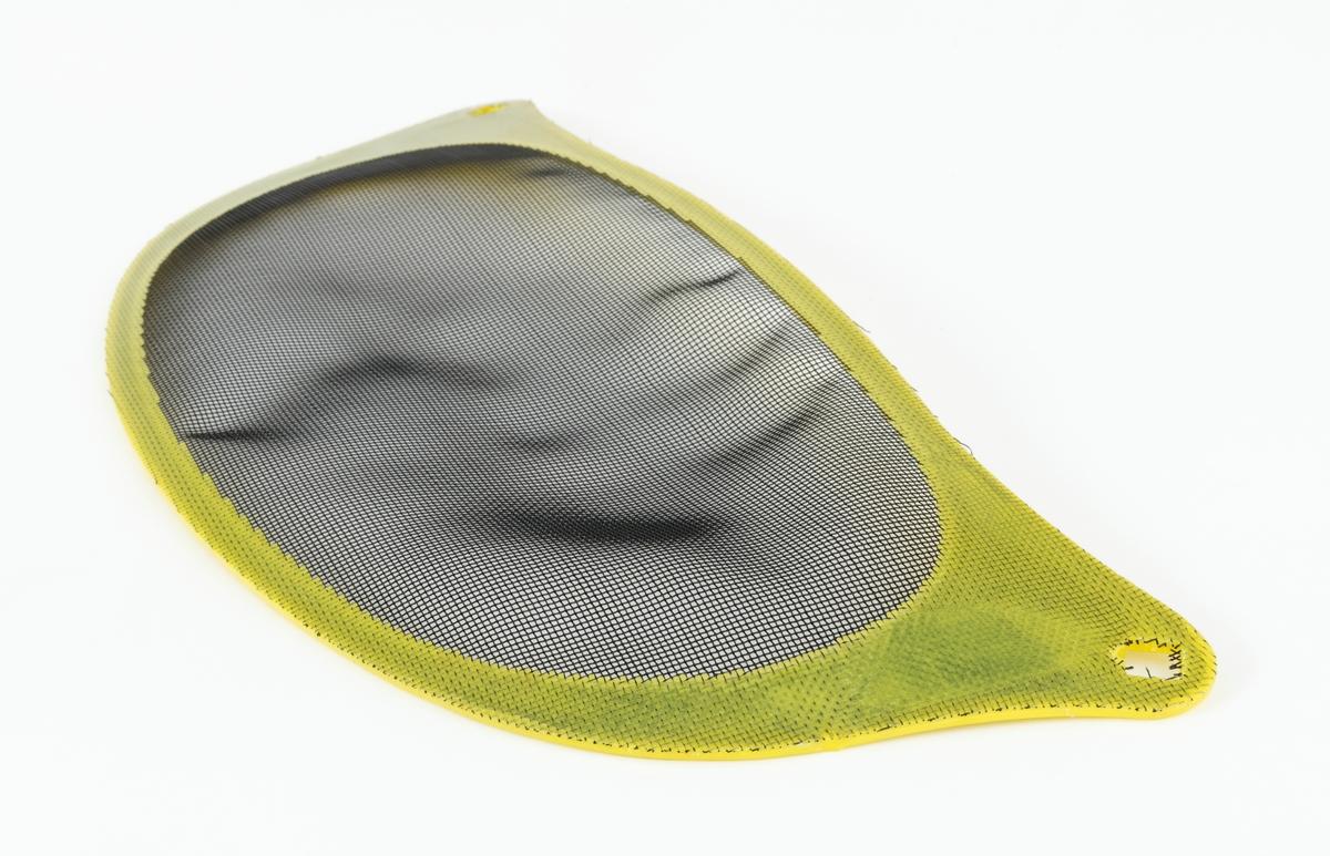 """Visir som festes til hjelm, skogshjelm, hoggerhjelm, for å beskytte brukerens ansikt og øyne. Visiret består av et finmasket nylonnett som er støpt inn i en ramme av plast. Rammas hjørner (""""ører"""") har firkanthull for innfesting i hjelm med trykknapp. (Trykknappfestene kan kjøpes løst til visirene.)"""