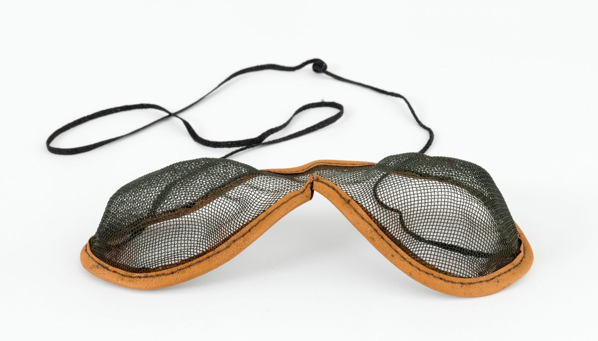 Brille, vernebrille, som brukes for å hindre at flissprut fra motorsaga treffer øynene. Vernebrillen består av en finmasket metallnetting som er festet i en innfatning av lær. Det er sydd fast en snor,  brillesnor, til innfatningen, slik at vernebrillen kan henge rundt brukerens hals når den ikke benyttes.
