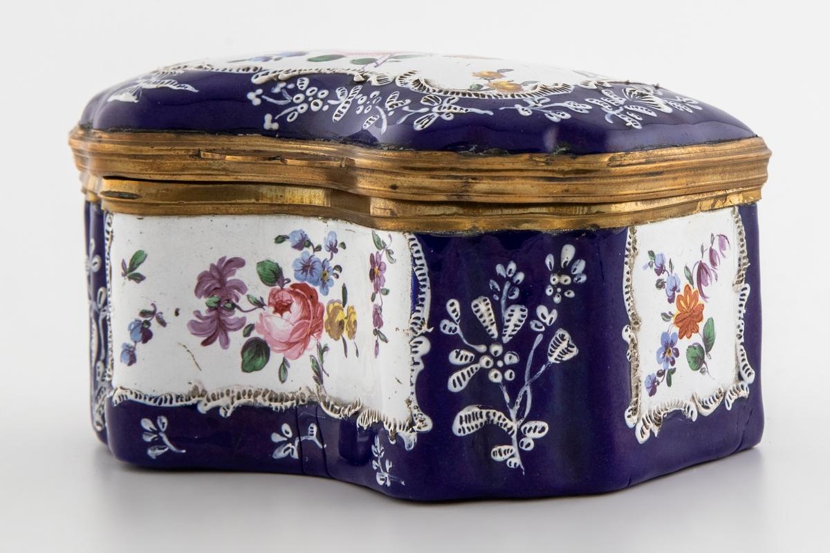 Skrin i metall med blåfarget opak emalje. Rektangulær grunnform med mykt bølgende forside samt hengslet lokk. Både utsiden og innsiden av lokket, samt veggene, er dekorert med hvite felter med påmalt blomsterdekor. Innsiden av lokket er dekket med melkehvit opak emalje med påmalte blomstermotiver. Inne i skrinet er det en forgylt holder for sandhus og blekkhus i klart glass.