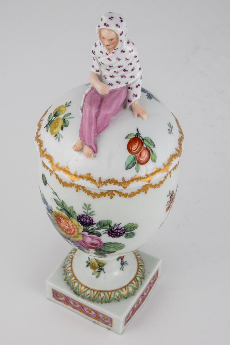 Urne i porselen med tilhørende lokk. Eggformet korpus med firkantet fot. Hvitt, ganske grovt og tykt gods. Hvitglasert med polykrom overglasurmaling, og gullborder langs kantene. Rundt korpus vises motiver med blomster, bær, frukt og rotgrønnsaker. Lokket er dekorert med blomster, bær og frukt. Lokknappen er utformet som en sittende kvinneskikkelse. Hun er fremstilt med benene i kors, lilla bukseplagg eller tettsittende skjørt, og er innhyllet i et sjal med små, lilla blomster.
