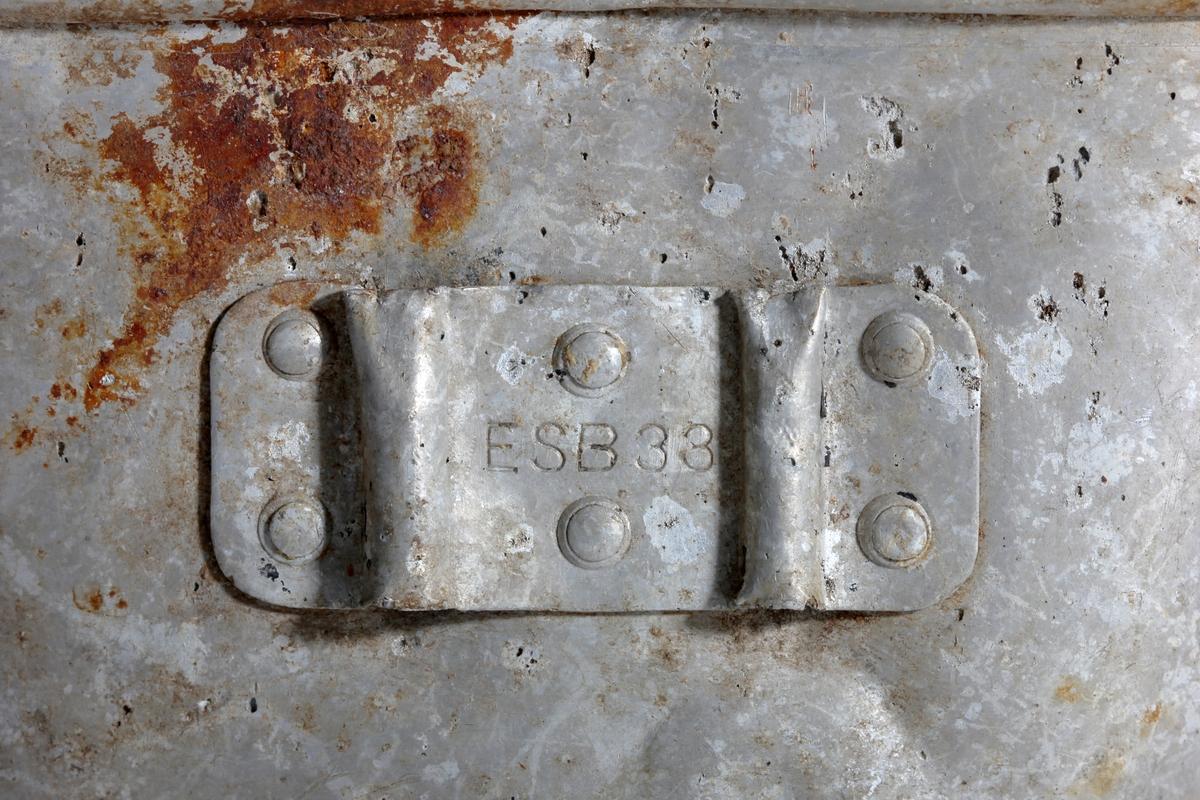 Oval drikkekopp til tysk feltflaske med bokstaver W.S under randen på baksiden og muligens tall 1, begge preget inn på samme måte. Noe rust som kan skyldes at det på funnstedet finnes store menger rusten piggtråd.