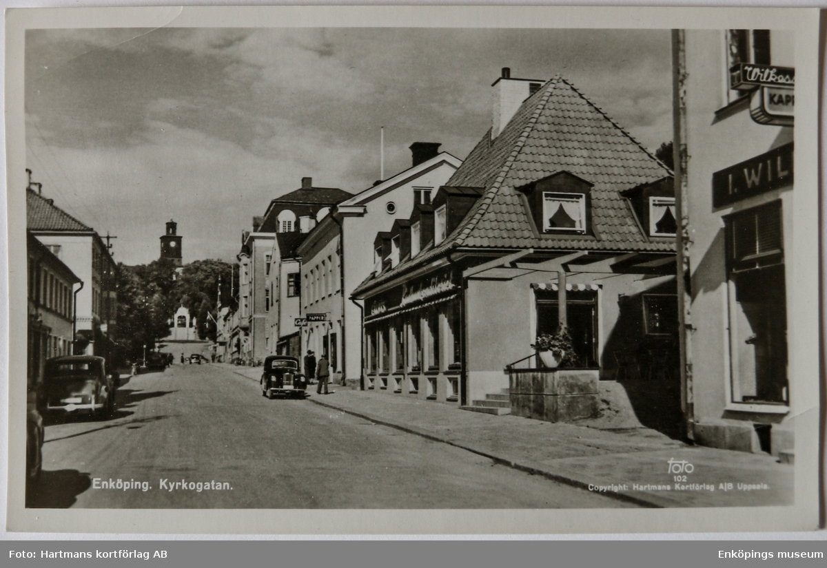 Kyrkogatan, Enköping. Huset mitt i bild med det kraftigt sluttande taket byggdes 1953. I huset låg det populära Rådhuskonditoriet. Huset längs till höger, nedanför Rådhuskonditoriet, är det Wilkessonska huset (tidigare kallat det Lagermanska huset). Det byggdes 1904 och på detta Vykort är det Wilkessons Kappaffär som huserar här. Huset revs 1990 och nytt hus byggdes upp i relativt liknande modell av det gamla huset.