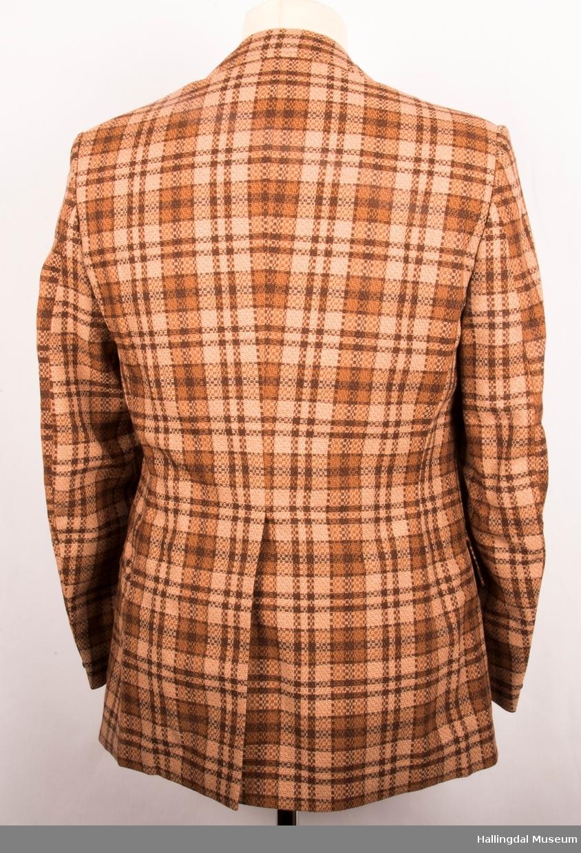 Kavaler dressjakke storrutete stoff, polyseter og ull. Brunt syntetisk silkefor. Jakka har skulderputer, store klaffer på lommene, 1 splitt bak.   Den er knept med 2 treknapper midt framme.  1 pynteknapp på hvert erme.  Store slag.
