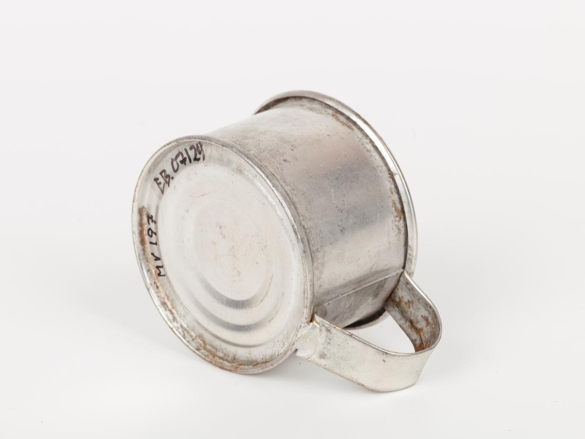 """Målet ser ut som en """"avstumpet"""", rund blikkboks med nedtrukket kant hvor det er påloddet en hank i topp og bunn. Det finnes ikke noe angitt mål. Full kopp er 0,5 dl."""