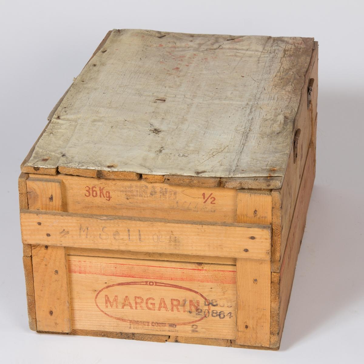 En margarinkasse fra  AS Margarincentralen Harstad med et hengslet lokk med slå i front slik at kassen kan låses med hengelås. Lokket er kledd med et voksduklignende materiale utvendig. Antagelig brukt sekendært til transportkasse/reisekasse