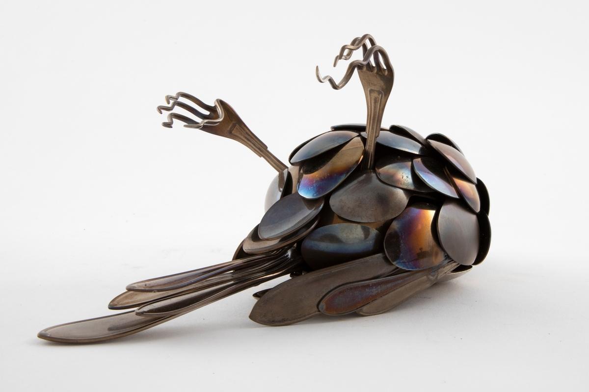 Skulpturen representerer en død fugl som ligger på ryggen med beina opp.