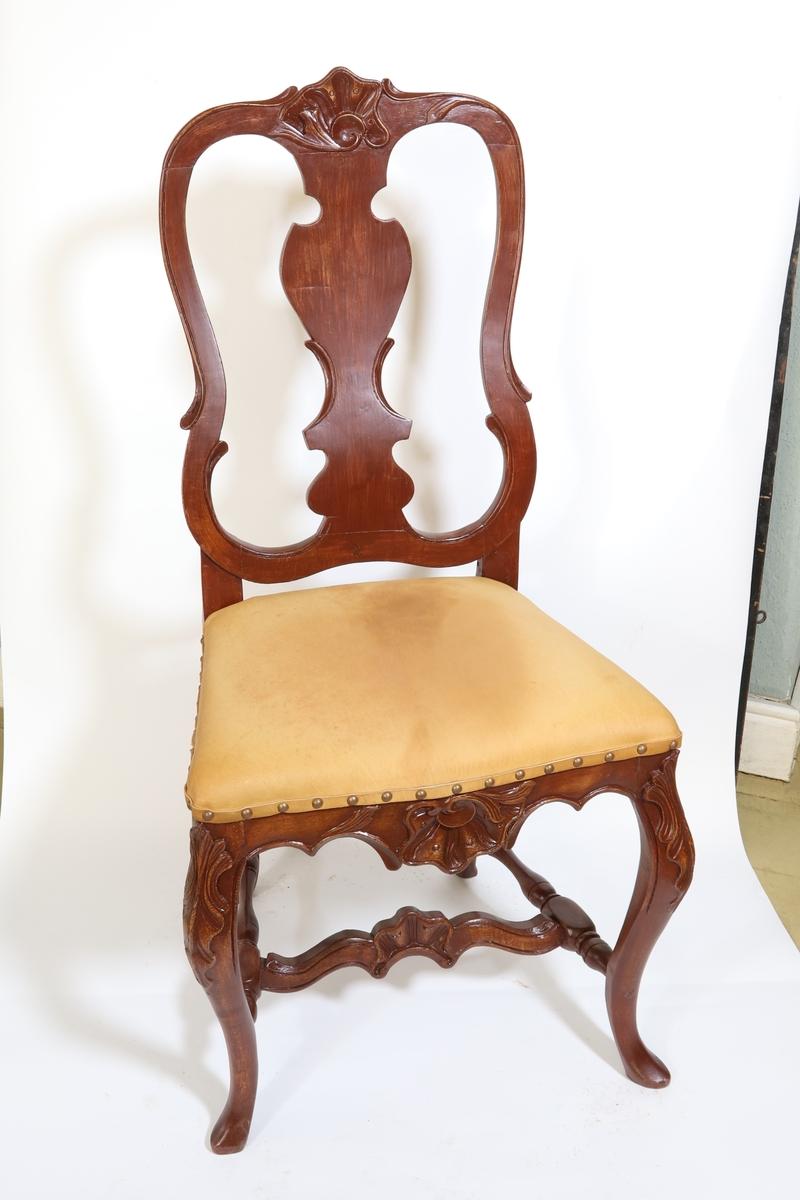 Stoler med trapesformet sete, polstret og trukket med lær. Nagler holder læret på plass langs nedre kant av sete. Fire stolben av tre de to i front er buet med utskjæringer i tre og de to bak har en mindre bue ved bunnen. Tre bindingsbrett, to fra bakre stolben til stolben i front. Et på tvers i midten. Utskjæringer i treverket i form av skjell.