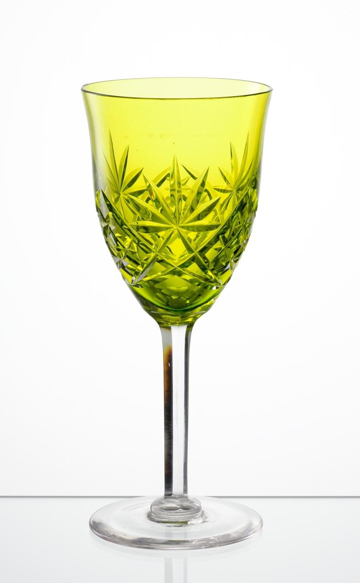 Vitvinsglas, svagt klockformad, gulgrön kupa med skärslipad dekor. Högt fasettslipat ben med slät fot.
