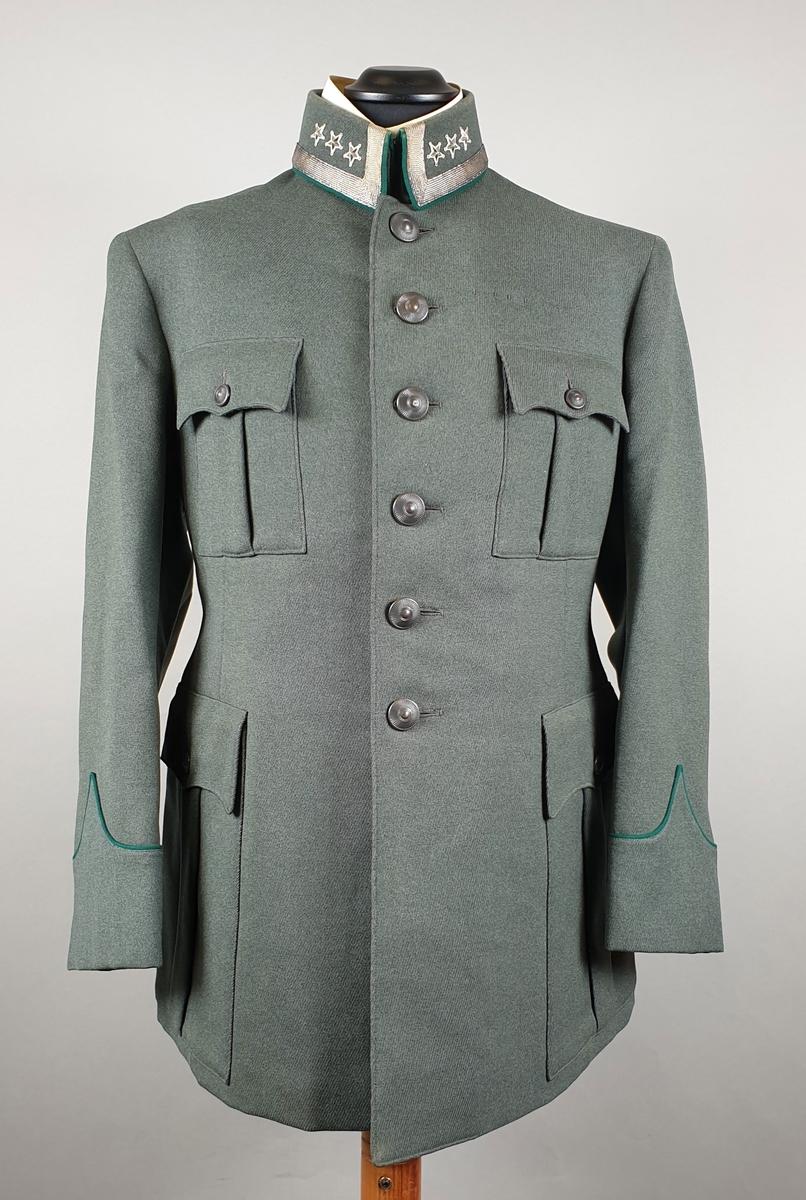 Grønn uniformsjakke av ull med krage med sølvbånd og to stjerner på hver side. To innsydde lommer nederst og to påysdde lommer på brystet. Mørkegrønne bånd på ermene. Enkeltspent. To knapper på ryggem over splitt. Pyntekragge av karton i halsen.