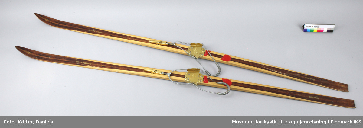 Tofarget treski med Kandaharbindinger. Bak bindingen er det påført deler i rød kunststoff for bedre feste med skoen. Helt bak har skiene en metallkant.