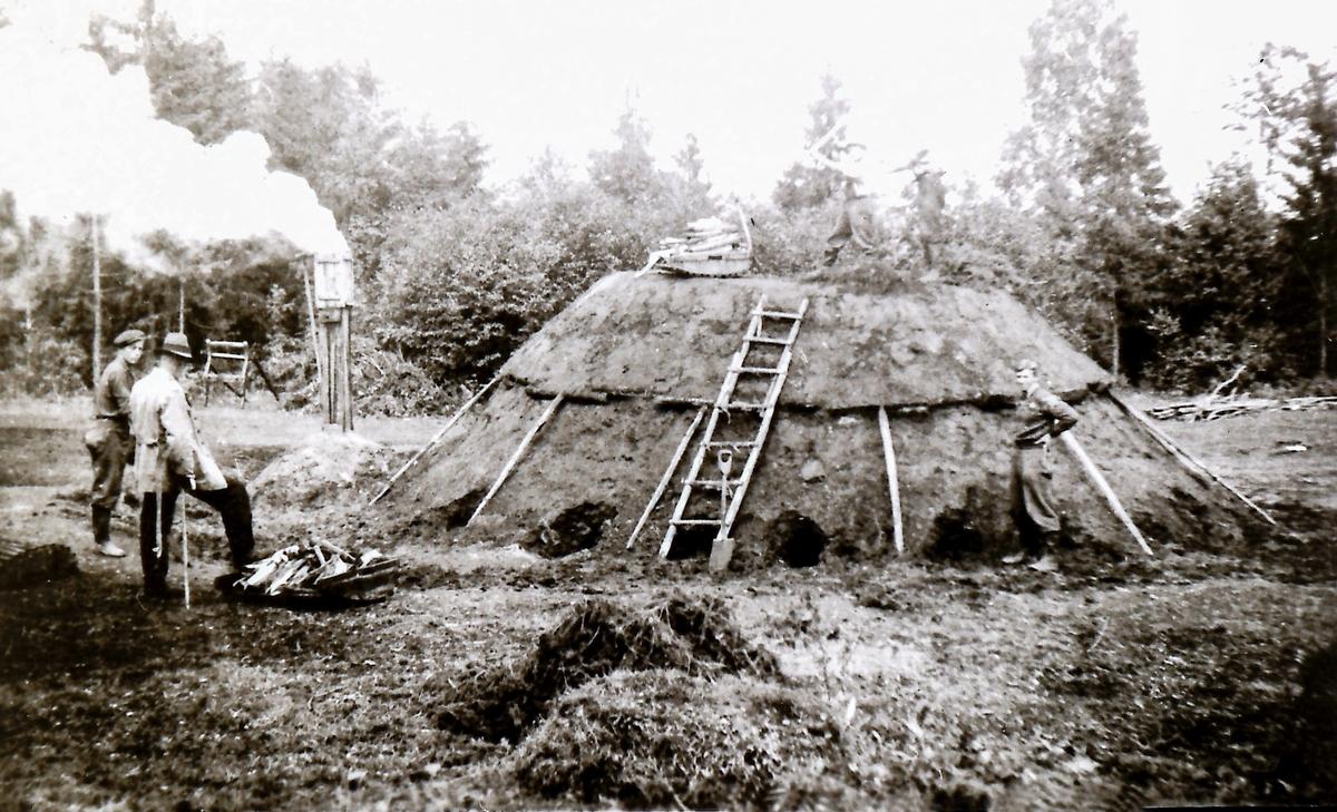 Milebrenning, mila er tildekket og tent (legg merke til dekket og trekk-systemet). Skogskolen i Kongsberg er med i øvingsfeltet.