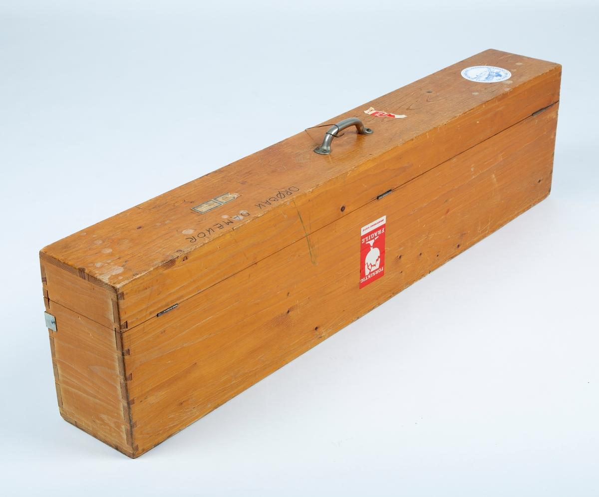 """Fane. Foreningsfane tilhørt Drøbak Damekor. A: Fanekasse, B: Fane, C: Tverrstag, D: Stang i 2 deler, E: Toppkule,  F: Bæreytstyr.  A: Kasse med lokk, håndak oppå lokk. Tre, antakelig gran.  l: 121. b: 17, h: 30.  B: Fane og snorer.  Kunstsilke. Lys blått stoff, falmet, kantet med gylden snor. Brodert stilisert lilje og tekst. """"DRØBAK DAMEKOR. STIFTET 1943"""" """"SANGEN HAR LYSNING"""" br: 110, h: 94, + frynser 9cm.  Snor med dusk i hver ende. Snor med gripetak i hver ende                                                         C: Tverrstag metall :br. 116.  D: Stang i 2 deler, aluminium: L: 118 (hver stang) E: Toppkule, metall:   h. 39, lyre h 32 i metall.  F: Bærebelte i lær:  l. 103 G: Lyre , metall: h: 32, b: 18"""