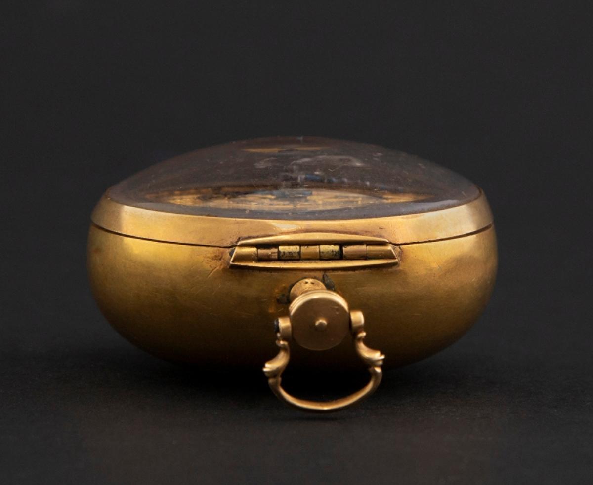 """Lommeur med ytre og indre kasse av gull. Ytterkassen er rikt forsiret i drevet og siselert arbeid. På baksiden fremstilles motivet """"Sauls omvendelse"""", omrammet av rokokkoornamentikk. Den indre urkassen er glatt med glasslokk. Urskiven er av gull med svarte romerske og arabiske time- og minuttall. Visere av stål. Kloben er gjennombrutt og gravert med ranker og maske."""