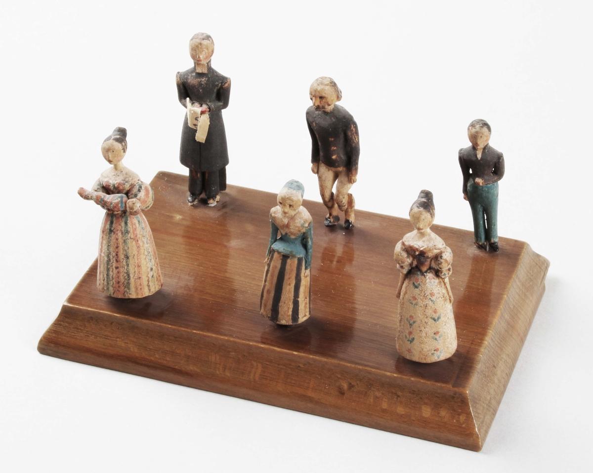 """Figurgrupp i trä. """"Symboliserar ett dop"""". 1830-tal. 6 stående figurer, i snidat trä, med handmålad dekor. I form av, präst, kvinna med barn i famnen, 2 kvinnor och 2 män. De sitter med stift, i rektangulär, brunbetsad- och lackad träplatta, med insvängda kanter.  Till denna figurgrupp hör konsolhylla BM 39798."""