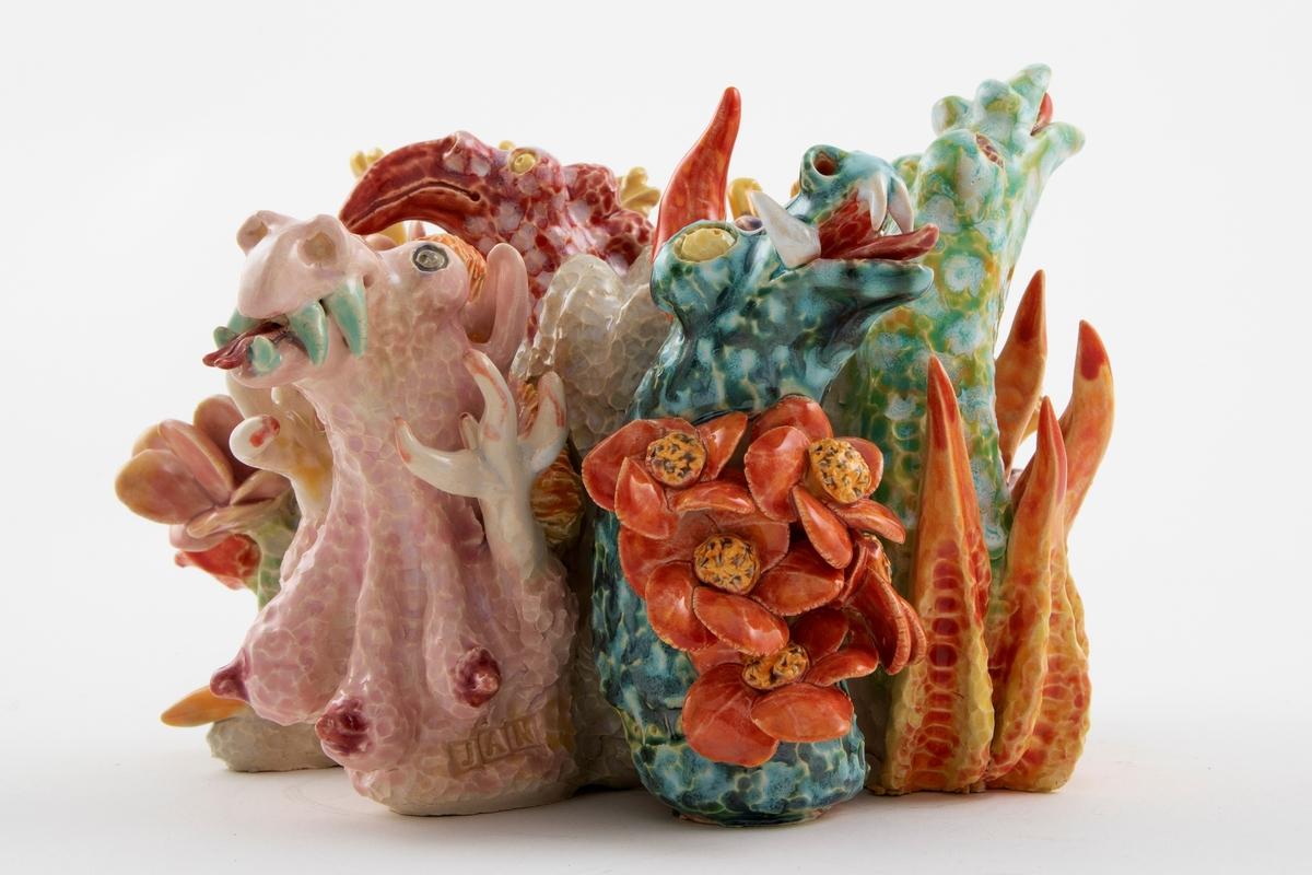 Komponert av fantasifigurer som minner om undervannsdyr, drager og flodhester.  Blomster og koraler. To dyreføtter med klør ut fra korpus.