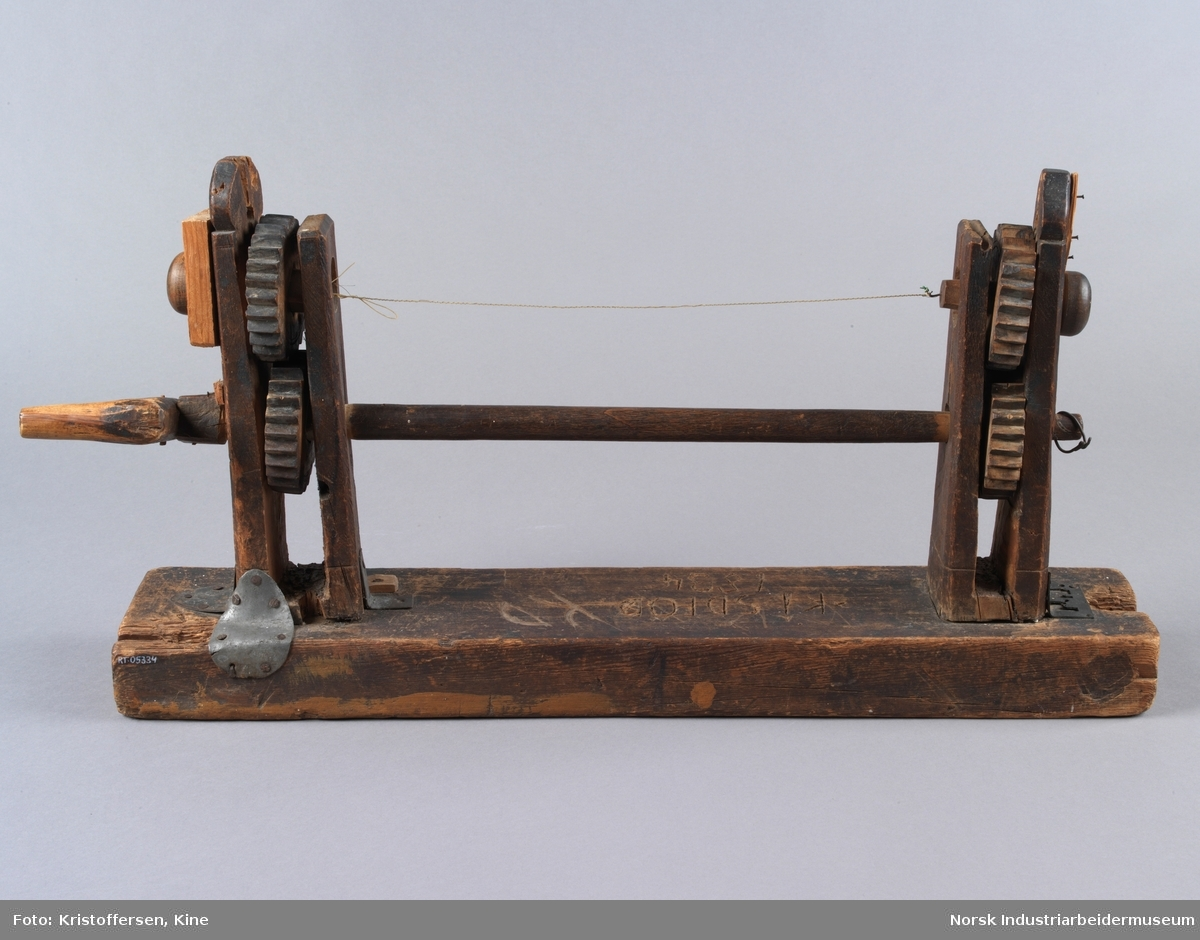 Strengelegger. Brukt til å tvinne felestrenger. Redskapet er primært i tre, men har festebeslag på bunnplate i metall. Avlang bunnplanke med to stående konstruksjoner koblet sammen med en avlang trepinne og tvinnetråd. To tannhjul på hver side, sveivearm kun på en side. Virker å ha noe mindre reperasjoner og treverk av litt nyere dato.