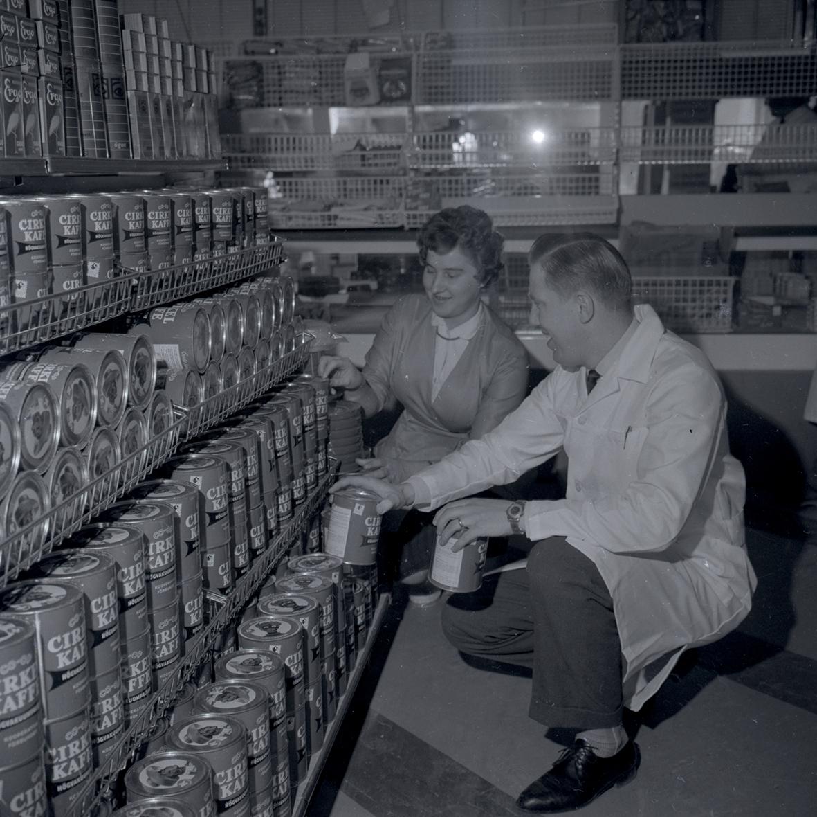 Bild tagen i samband med invigning av Konsum. Man och kvinna vid kaffehyllan.