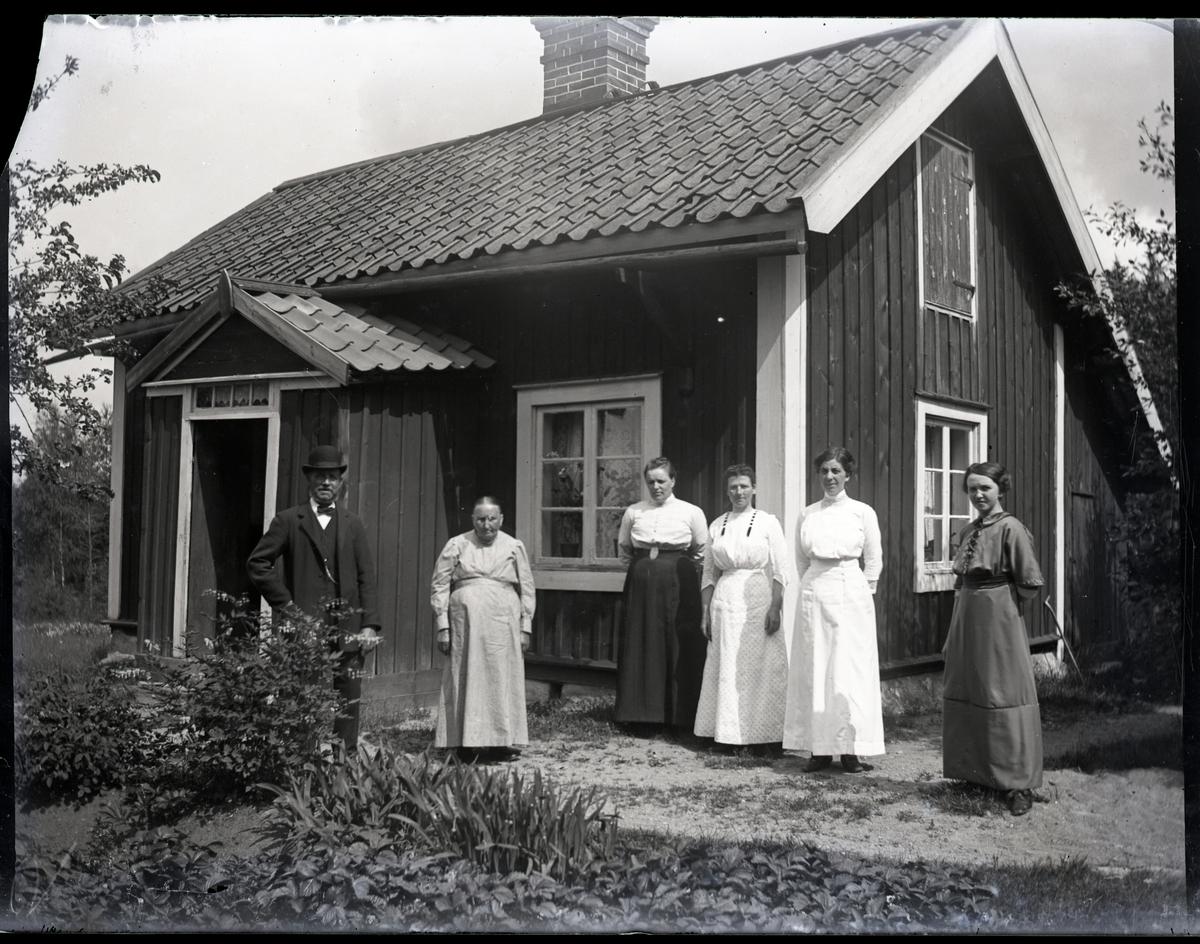 En man i hatt och fem kvinnor stående utanför torp. Trädgårdsland med bl.a. löjtnantshjärta.