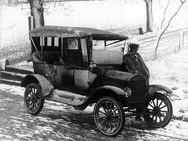 En nedisad bil står på Brahegatan i Gränna vid torgets södra uppfart. En man i rock, halsduk och mössa med öronlappar står på andra sidan bilen, lutad mot densamma. Han har en liten snöhög på mössan.
