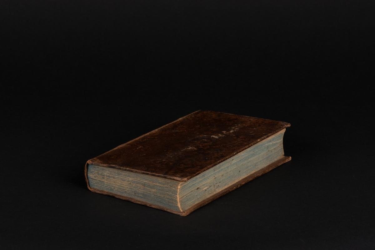 Nya testamentet i läderband och gröntonat snitt, tryckt 1851. På sidan 62 (Matteus kapitel 21-22) ligger en instucken lapp som bokmärke. På sidan 180 (Lukas kapitel 11-12) ligger ett bokmärke i form av en treklöver. På sidan 184 (Lukas kapitel 12) ligger en lapp med påskrift och på sidan 274 (Johannes kapitel 14-15) en lapp utan påskrift. Sidan 572 har ett nedvikt hörn (Johannes kapitel 1-2).