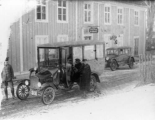 En buss med reg nr F231 står parkerad utanför Hotell Brahe i Gränna. Det är snöslask på vägen. Intill bussen står chauffören Harry Håkansson. Till vänster står en okänd man i chaufförsuniform - möjligen Eklund.
