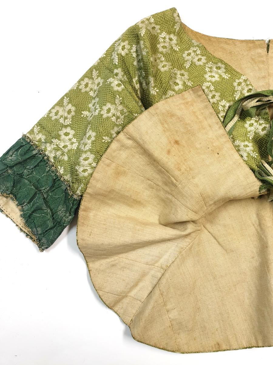 Kofta, grön sidenbrokad, 1700-tal, grönt fjälligt mönster med vita blommor, samt mörkgrön påsättning på ärmarnas nedre del. Fyra band att knyta över bröstet. Indraget liv.