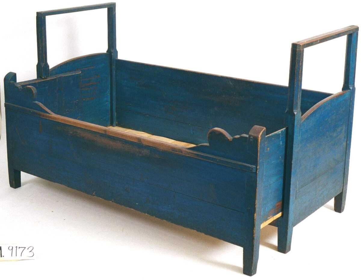 Seng fra midten av 1700 tallet,  malt  begyn. 1800 tallet.   Furu,  sterkt blåmalt, underliggende rødbrun maling.  Seng med svakt rundede, like høyt fot- og hodegjerde, med 8- kantete  hjørnesøyler med rett tverrligger. Bakveggen har rett karm  nesten  like høy som hode- og fotgjerde, forsiden en karm med buet  kontur i  hjørnet mot stolpene. Kortside med sidekarmer kan løftes frem.  Tilstand: litt slitt i blåmalingen, det rødbrune skinner  igjennom.  Sterkt markspist, særlig i bunnplatene i begge deler, disse er  fjernet og brent, resten behandlet med Basileum.