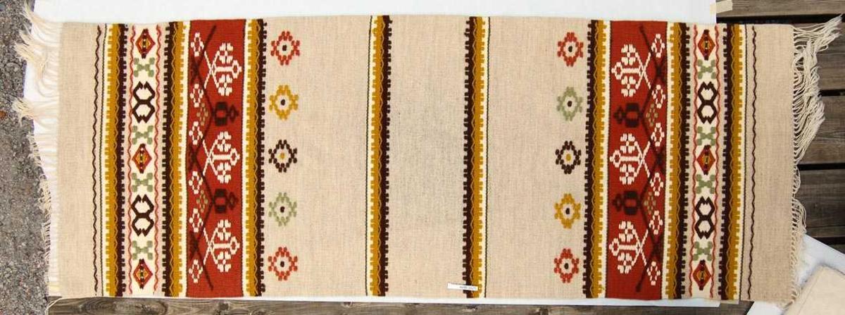 Mønstervevd løper i ull med renning i bomull. Deler av mønsteret i relieff som minner om broderi.