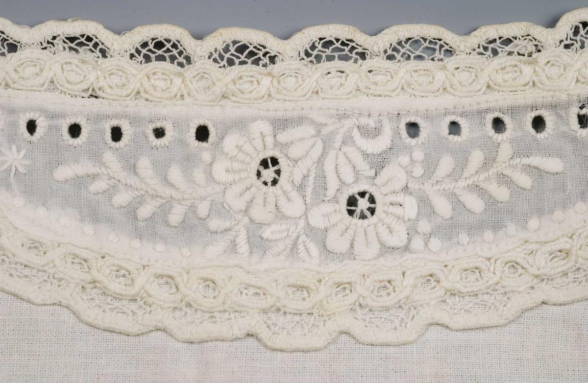 Hvite mansjetter med 3 knapper til å lukke mansjetten med. Dekorert med broderier og kniplinger langs håndleddet.