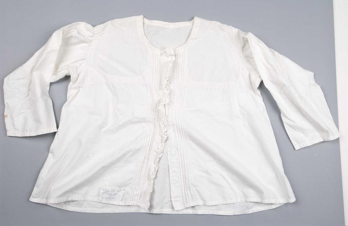 Hvit skjorte med lange ermer uten mansjetter. Lukning foran med 3 kanpper øverst. Sydd av to typer stoff, det ene formet som bærestykker. Pyntet med biser og blonder foran langs lukningen. Midjekort sterkt skrånende.