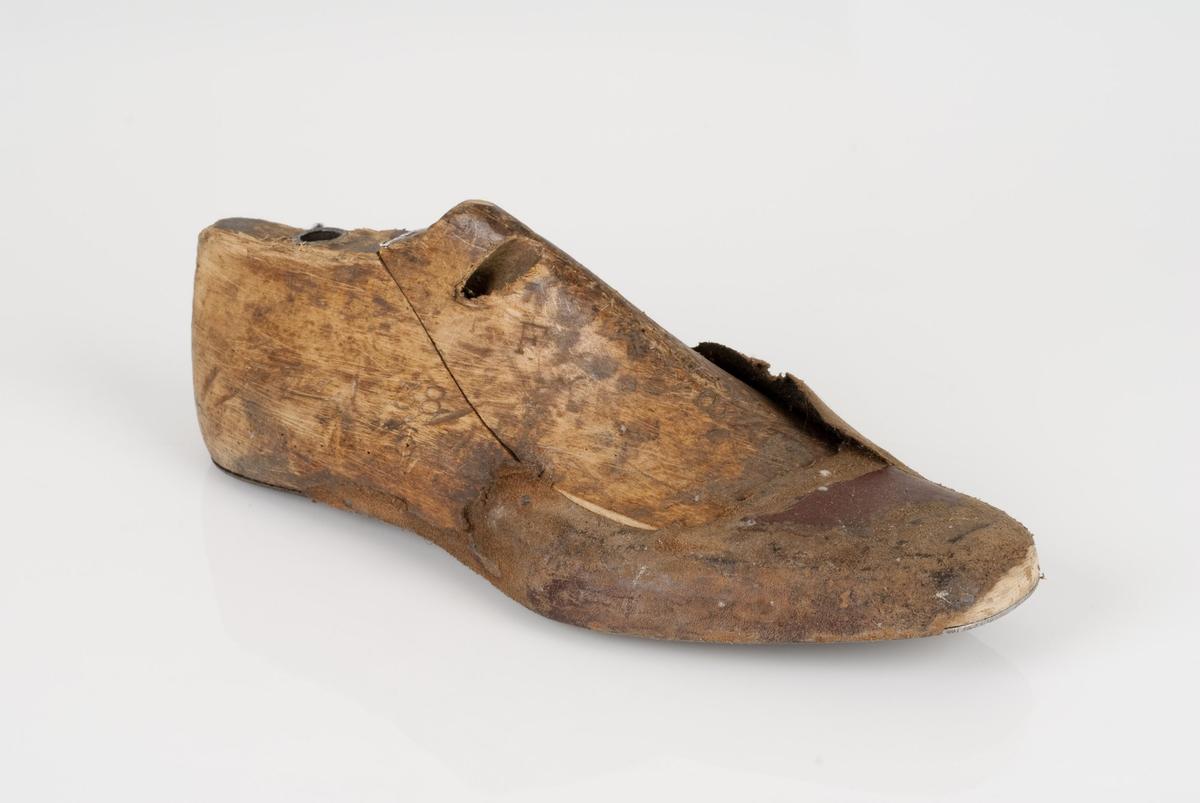 En tremodell i to deler; lest og opplest/overlest (kile). Høyrefot i skostørrelse 38, og 6 cm i vidde. Såle av metall. Lærhusk på lesten.