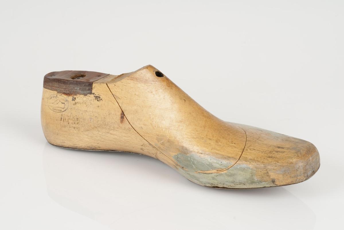 En tremodell i to deler; lest og opplest/overlest (kile). Venstrefot i skostørrelse 44, og 8 cm i vidde. Lestekam i skinn. Såle i metall.