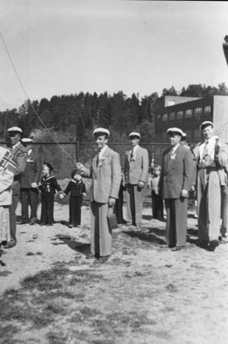 Medlemmer av Oppegård mannskor stående oppmarsjert foran gjerde.