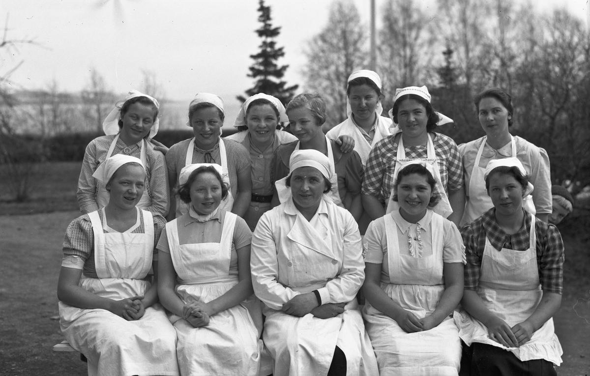 Gruppe kvinner i hvite uniformer. Kan være fra Landbruksskolen på Toten.