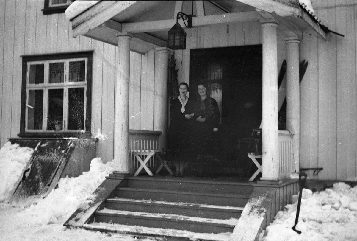 To kvinner ute på trappa vinterstid.