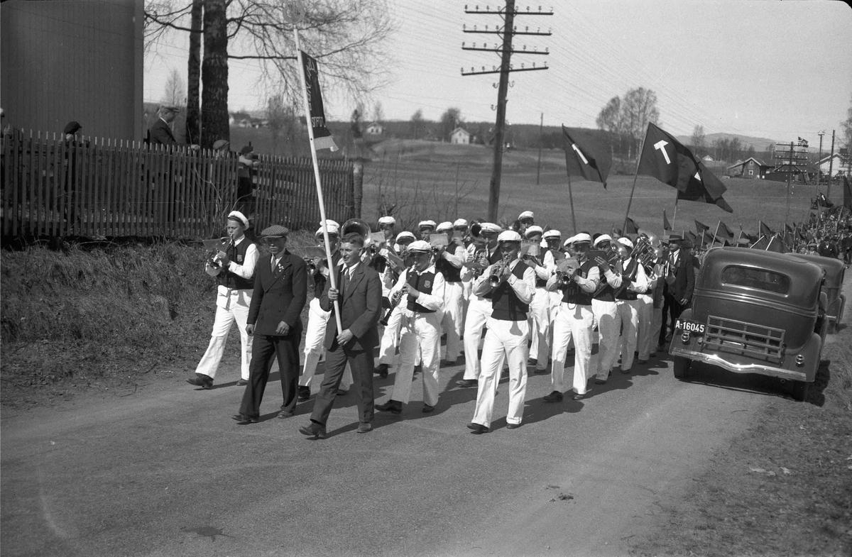 """Bøn musikkorps foran 1. maitog. """"Bøn"""" på fanen og hammer på flaggene. Albert Karlsen bærer fanen. Sannsynligvis i 1935."""