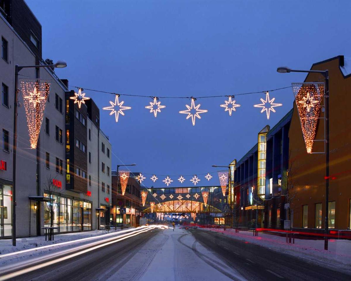 Julebelysning.  Julegate ved Strømmen Storsenter. Hvite stjerner og lys i kremmehusfason henger nedover gaten og gir allèeffekt. Overgang mellom storsenter og parkeringsringshus er dekket med lysteppe og danner fondmotiv for allèutsmykningen.